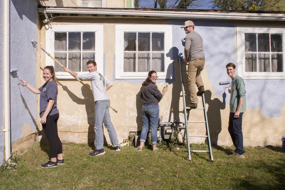 Students painting side of a building